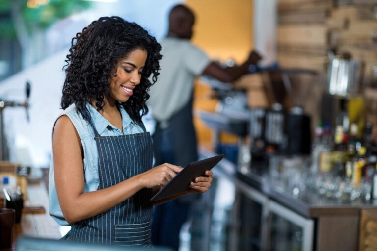 Smiling Retail Worker Using Digital Tablet